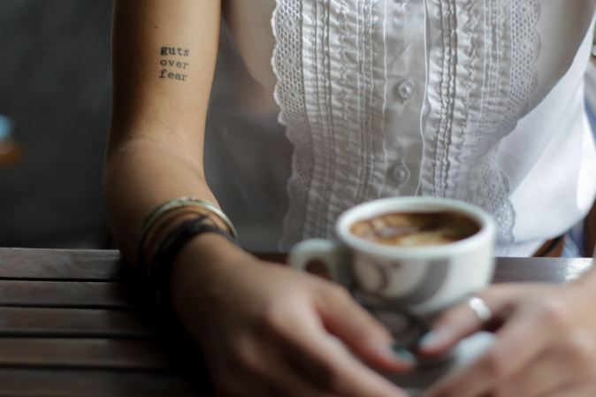 Picture of woman sat at a table with cup of coffee with 'Guts over fear' tattoo