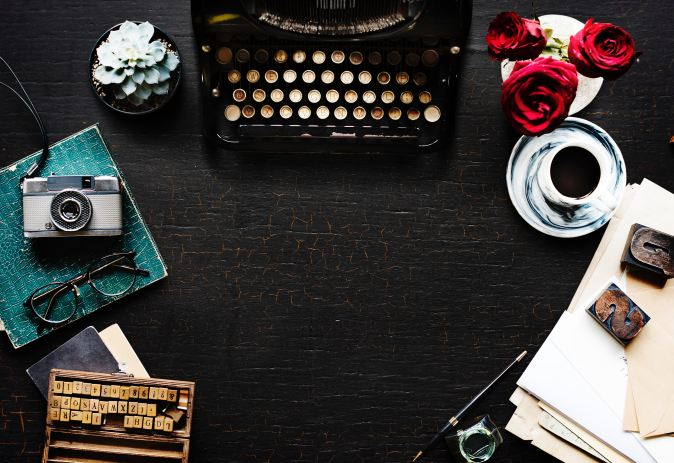 Picture of a desk with typewriter, coffee, flowers etc