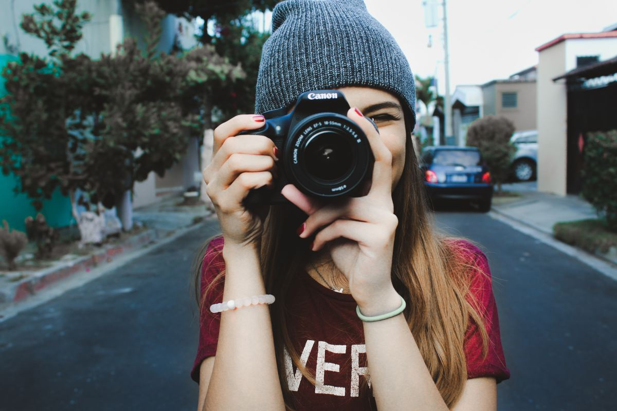 Picture of a girl taking a picture with her camera wearing a t-shirt and beanie hat in a street