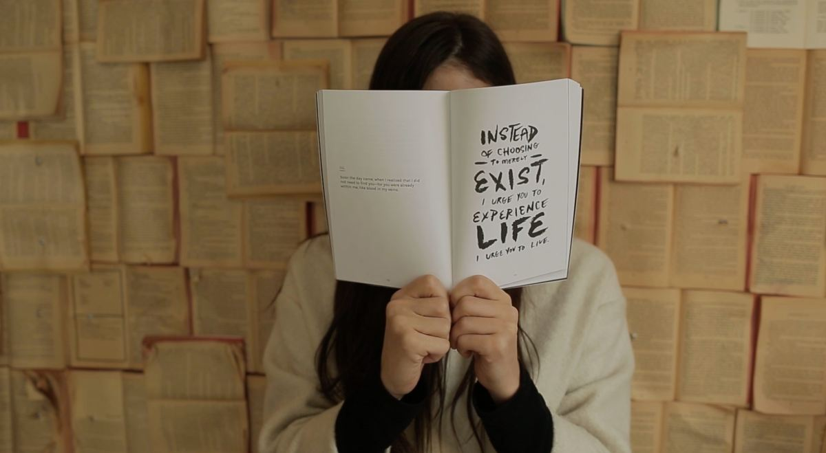 Picture of a girl standing infant of a wall full of books holding up a book about life
