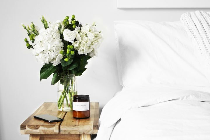 Picture of flowers and candle on a bedside table next to a bed