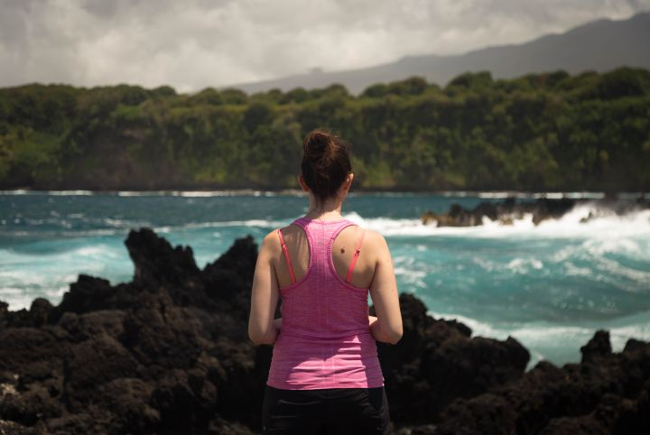 Picture of a woman's back in gym kit as she looks out to sea