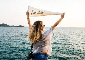 Girl holding freedom flag by the sea