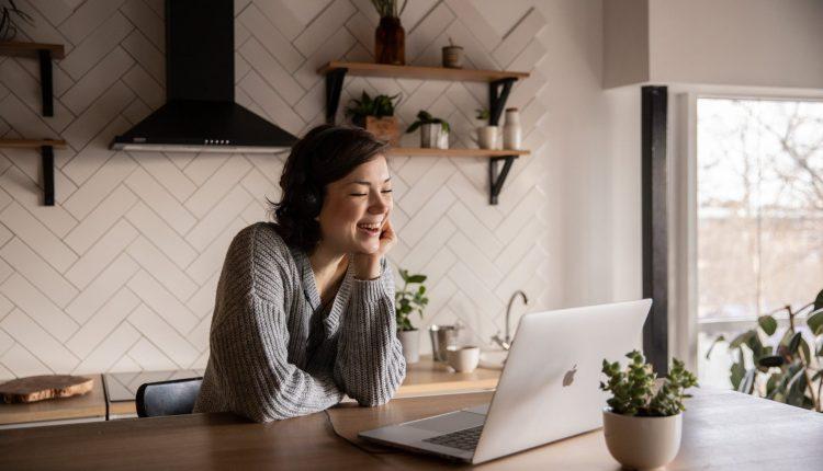 smiling woman talking via laptop
