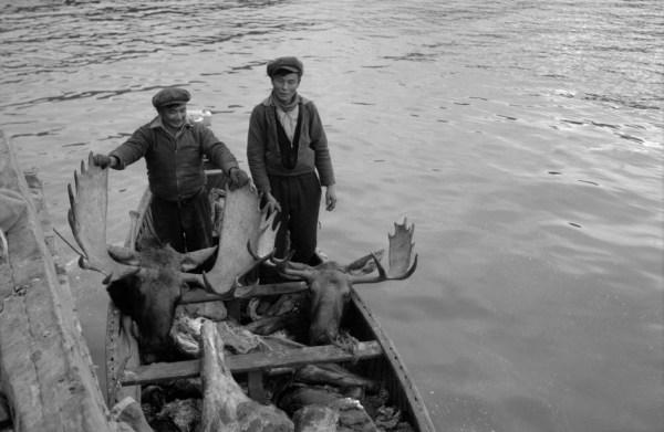 3. Edward Blondin (holding horns) and Jean Baptiste in boatload of butchered moose at Port Radium Busse/NWT Archives/N-1979-052-1838