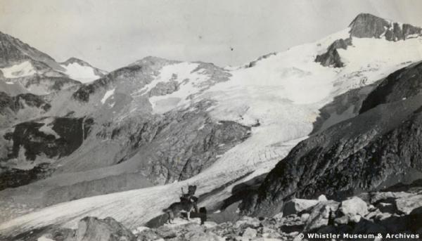 Hunter and dog in the Fitzsimmons Range near Whistler Mountain, 1920s. Overlord Mountain and Glacier in background. Courtesy Whistler Museum and Archives Society.