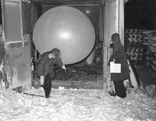 Preparing to launch a balloon with radiosonde after preparing them in the inflation shed at Resolute, 1949. Alan Faller personal collection, reproduced with permission.