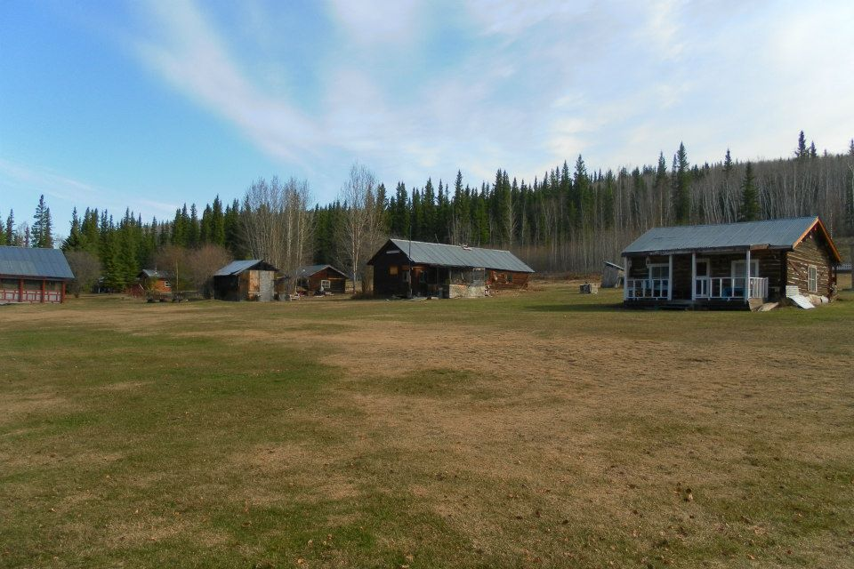 The photo depicts original cabins dating to about 1900 at Moosehide Village.