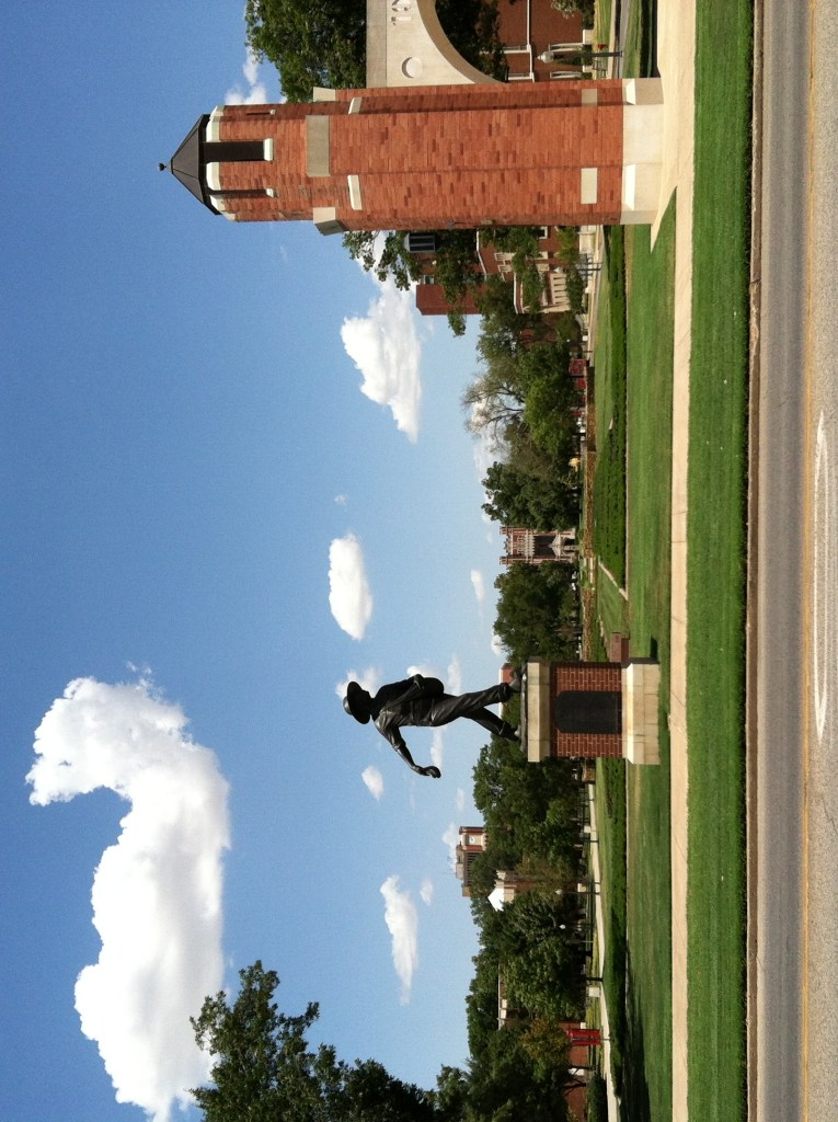 "The grounds of the University of Oklahoma. A statue of a ""seed-sower"" on a pedestal on a green lawn, with decorative architecture to the right."