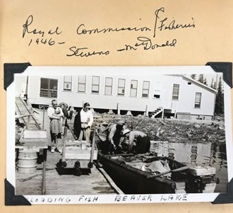 Fisherman loading fish off the boat at Beaver Lake while Gus MacDonald observes.