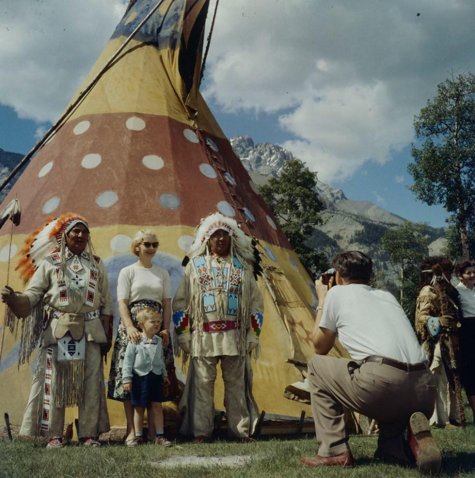 A man taking a photograph of a woman and child posed with men wearing headdresses and beaded clothing during Banff Indian Days. [Homme photographiant une femme et un enfant prenant la pose avec des hommes portant des coiffures en plumes d'aigles et des vêtements ornés de perles, lors des jours de festivités indiennes à Banff]