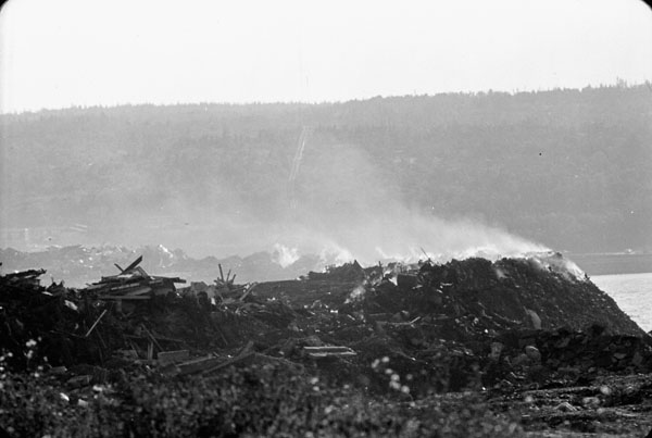 A garbage dump with smoke coming off it.