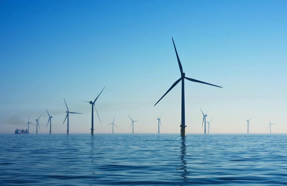 Windmills standing in the sea against a clear blue sky.