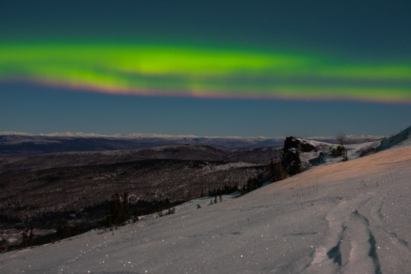 Aurora Borealis shimmering above a snow covered mountainside