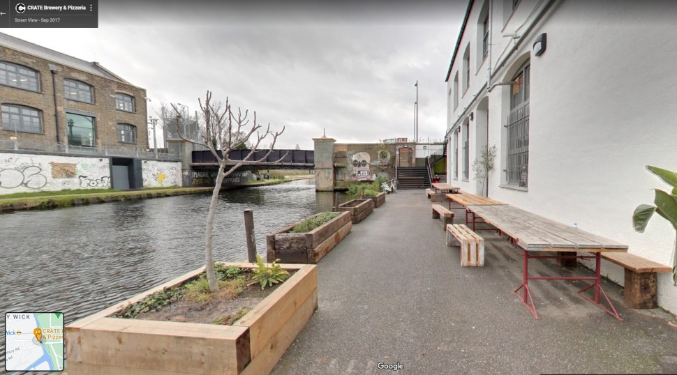 Google Street View screenshot. Wooden tables and benches on a canalside path. There are wooden planters on the bank of the canal and in the background a bridge and post-industrial building have been graffitied.