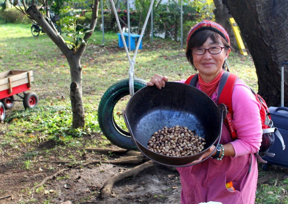 A woman holds a container that has freshly roasted ginko nuts in it.