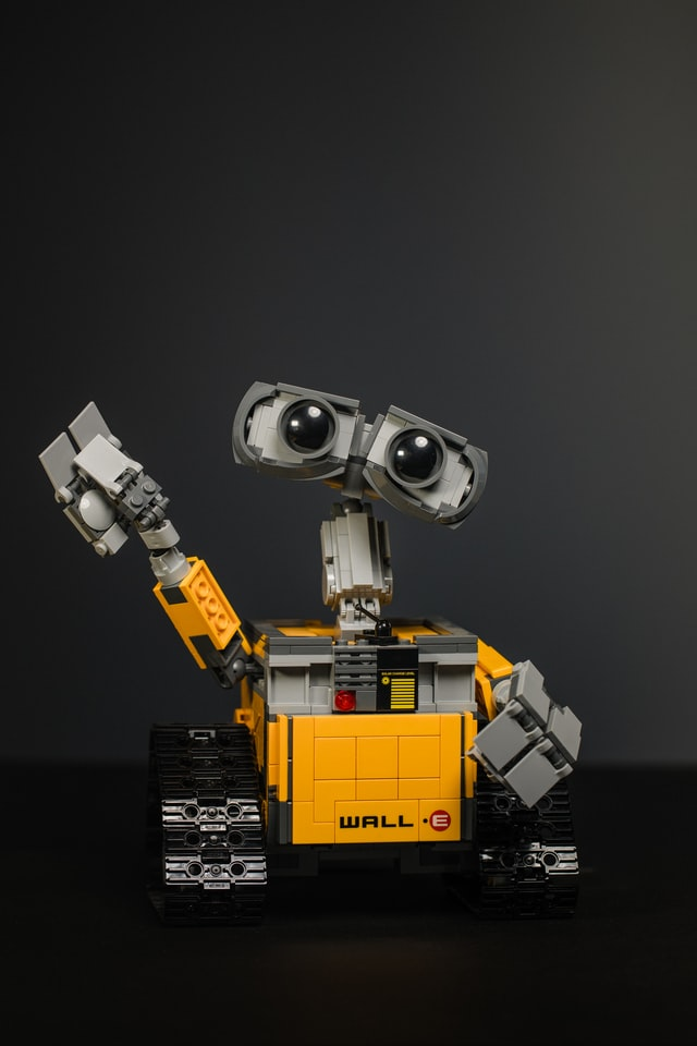 Robot with large eyes, yellow body and friendly wave