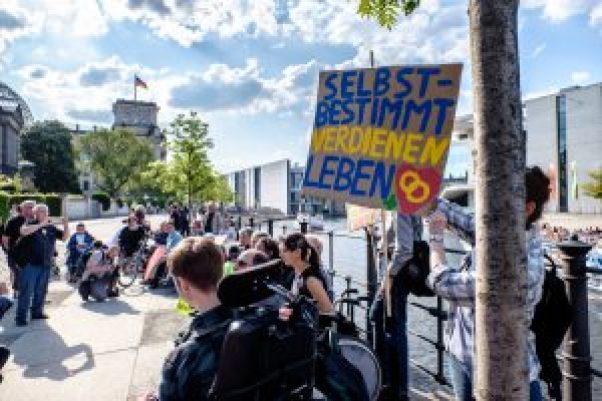 """Protest zum Teilhabegesetz vor dem Bundestag mit einem Plakat: """"Selbstbestimmt leben!"""""""