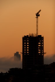 Dawn silhouette of office block with crane