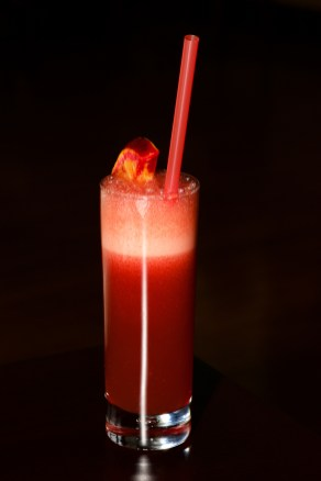 Tall glass of red sherbet with straw