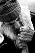 Mono bearded tramp in beanie lighting cigarette