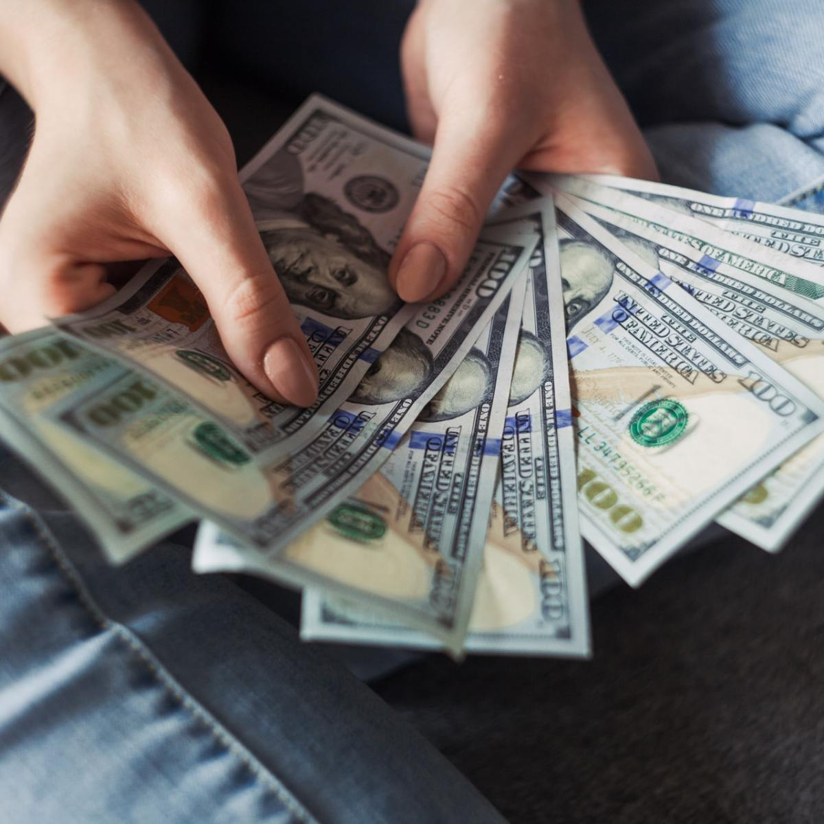 Person counting money. 7 smart ways to spend your tax refund