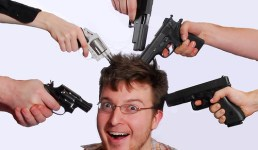 image of a man with multiple guns pointed at his head