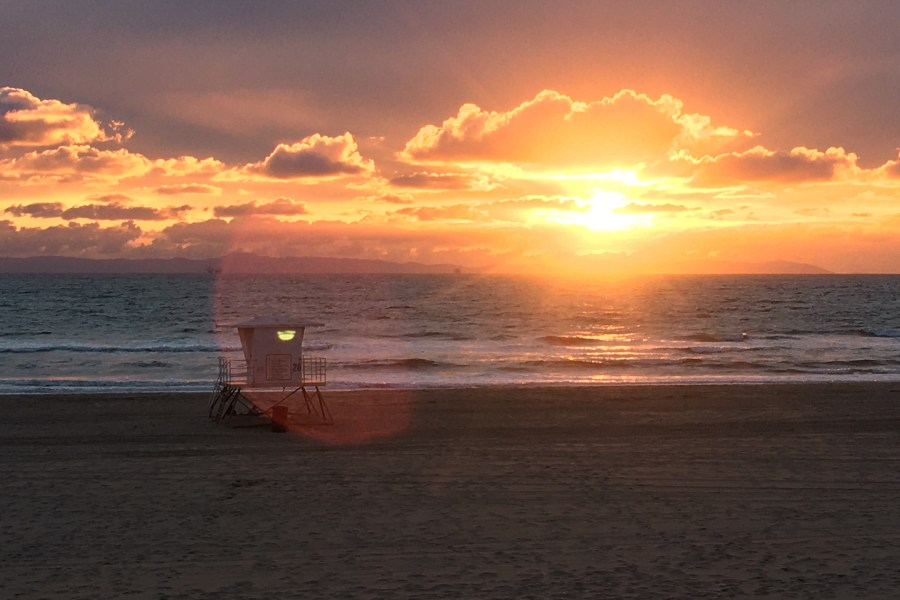 shoto of the beach at sunset with a lifeguard tower in the midground