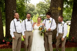 bride laughing with groomsmen in outdoor country chic wedding portrait by MN wedding photographer Nicki Joachim Photography of Owatonna Minnesota
