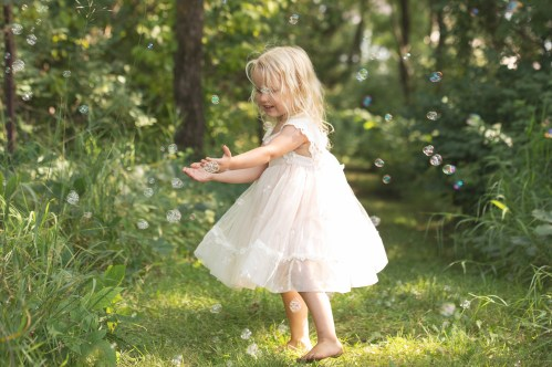 young girl playing with bubbles outside in the forest in a lifestyle child portrait by MN Child Photographer Nicki Joachim Photography of Owatonna Minnesota