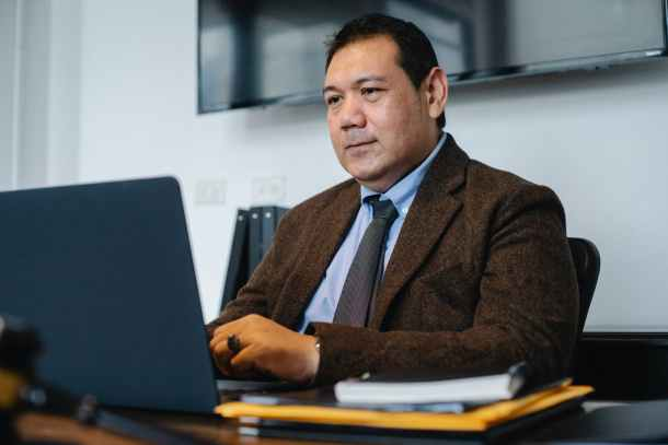 focused ethnic businessman using netbook while working in office