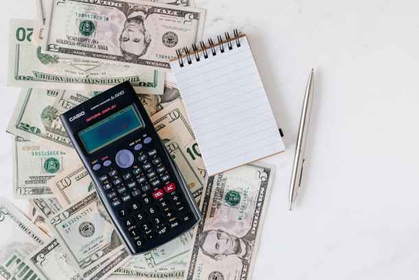 calculator and notepad placed over stack of usa dollars