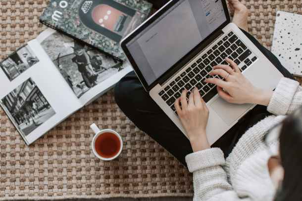 crop young businesswoman using laptop while drinking tea at home
