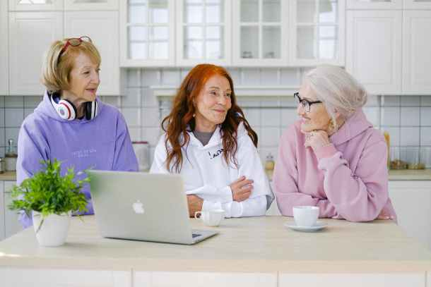 cheerful aged women friends communicating while sitting at table at home