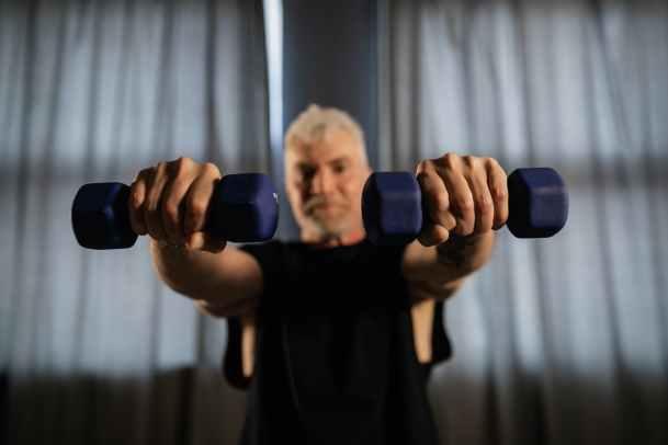 an elderly man lifting dumbbells