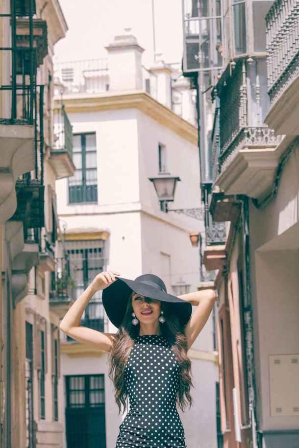 stylish woman in hat on street between buildings