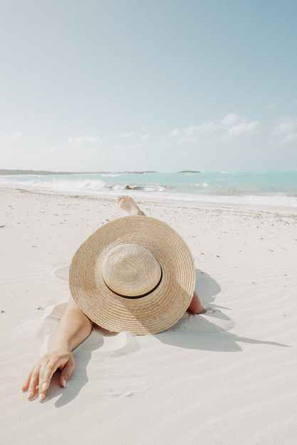 unrecognizable woman in hat lying on beach