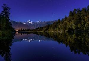 Shooting star reflecting in lake Matheson New Zealand