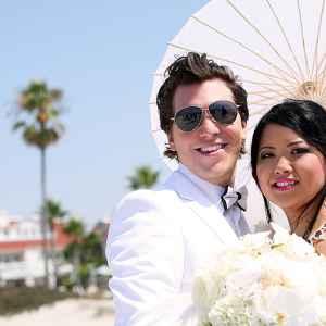 bride and groom with parasol at Coronado beach wedding