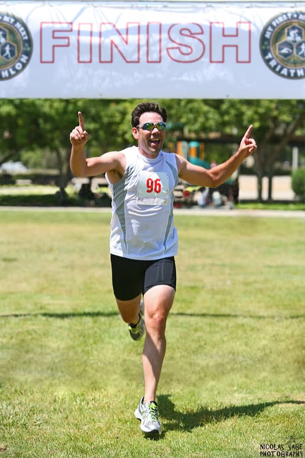 photo of male athlete running across the finish line