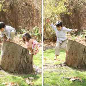 boy jumping off of tree stump