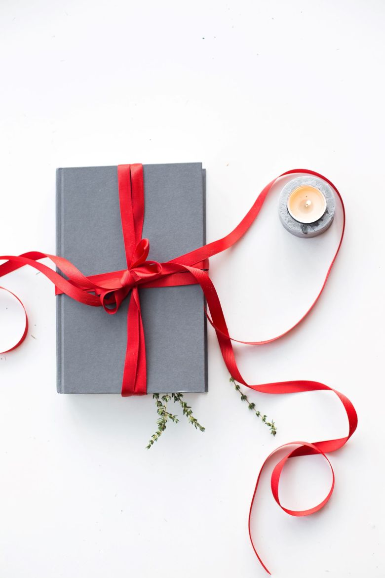 gray book wrapped with red ribbon beside tealight candle