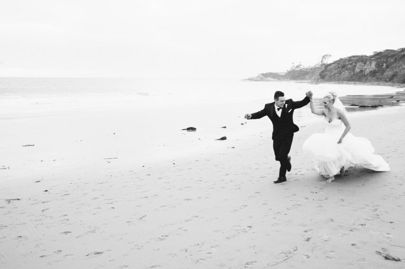 bride and groom running on beach Monarch beach resort wedding photographer nicole caldwell