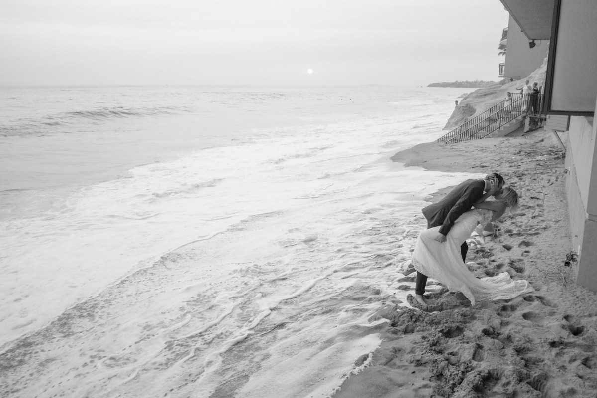 groom dipping bride on beach wedding photos surf and sand resort laguna beach