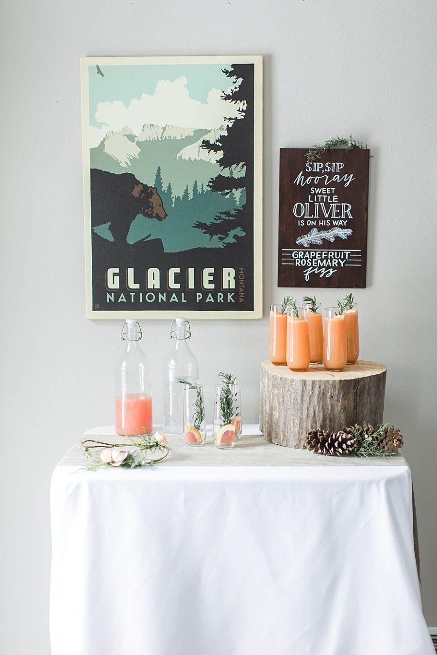 Vintage Glacier national park poster for baby shower styling with rosemary grapefruit spritzers styled on wood round