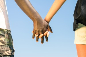 Multiracial couple walking hand in hand against a blue sky - Con