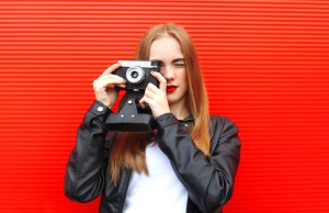 Fashion pretty woman with old retro camera over red background