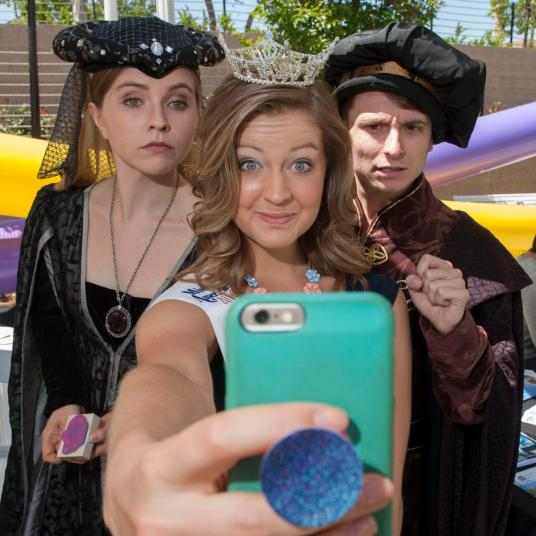 Miss City of Orange Nicole Renard takes a sefie with theater majors Gracie Truex, as Lady Hildegard, and Drew Petriello, as Duke Jameson, during the grand public opening of the new Musco Center for the Arts at Chapman University Saturday. ///ADDITIONAL INFO: musco.0403.kjs --- Photo by KEVIN SULLIVAN / Orange County Register -- 4/2/16 covering the grand public opening of Chapman University's new Musco Center. Gets going at 11 a.m. MUSCO CENTER INVITES YOU to a FREE OPEN HOUSE & ARTS FESTIVAL THIS SATURDAY, APRIL 2 ! If youÕve been wanting to get inside Chapman UniversityÕs new Musco Center for the Arts to explore and experience its beauty and acoustic splendor, this Saturday is your opportunity! Join us for a full day of FREE performances on FIVE STAGES inside and outside the Center, featuring the Chapman Hall-Musco Conservatory of Music in the largest collaboration of student and faculty ensembles ever (at 4:30 pm), three top world music/rock/jazz/fusion bands (MexicoÕs Troker, VancouverÕs Delhi 2 Dublin, and the Stooges Brass Band from New Orleans) on the World Stage, Chapman student performing groups, childrenÕs performances, local music/dance/choral and theatre groups, Pacific Symphony at 7:30 pm (sold out, but a limited # of tickets may become available at 6:30 pm) and MUCH MORE. More than 600 performers and 50 ensembles will be on the stages throughout the day! 4/2/16