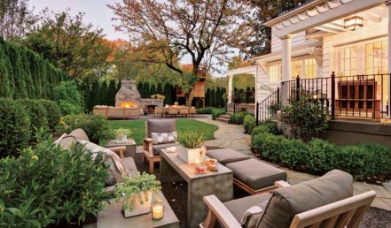 The garden at the rear of the home is planted with tall evergreens for privacy. Hardscaping includes a fireplace from Stone Sculptures, Pennsylvania bluestone and gravel paths. Gloster seating in the foreground, from Fishels, wears weather-resistant Sunbrella fabric. Leonard custom-designed the furnishings by the fireplace, made by Terra Furniture.