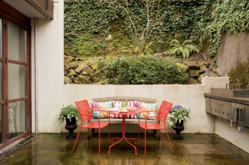 A red lacquer table and chairs complement the teak bench that also came with the house. In-door/outdoor fabrics in brightly colored hues cover bench pillows and make seating more comfortable.